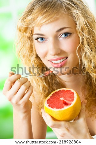 Portrait of young happy smiling woman eating grapefruit at home - stock photo