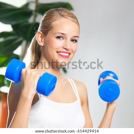 Portrait of young happy smiling woman in sportswear, doing fitness exercise with dumbbells, at home. Healthy lifestyle, training and individual sports concept.