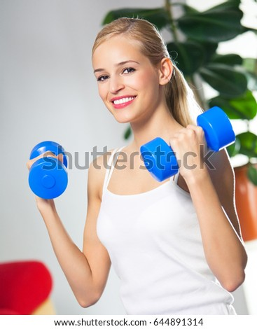 Portrait of young happy smiling woman in sportswear, doing fitness exercise with dumbbells, at home. Health lifestyle, weight lossing and workout concept shot.