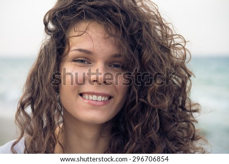 Portrait of young happy smiling woman on the coast in the summer. A woman with brown curly hair resting day on the beach in windy weather. Close up picture. - stock photo