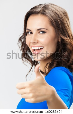 Portrait of young happy smiling woman showing thumbs up gesture, over grey background