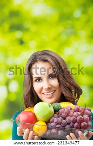 Portrait of young happy smiling woman with plate of fruits, outdoor, with copyspace