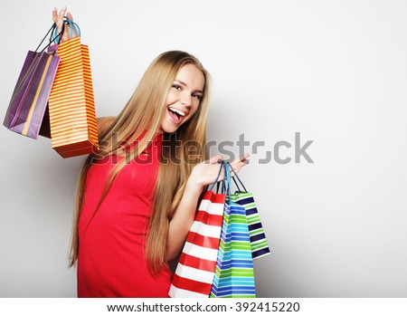 Portrait of young happy smiling woman with shopping bags, over white background - stock photo