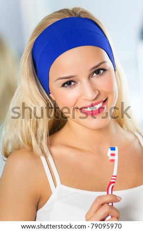 Portrait of young happy smiling woman with toothbrush at bathroom