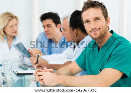 Portrait Of Young Happy Surgeon With His Team - stock photo