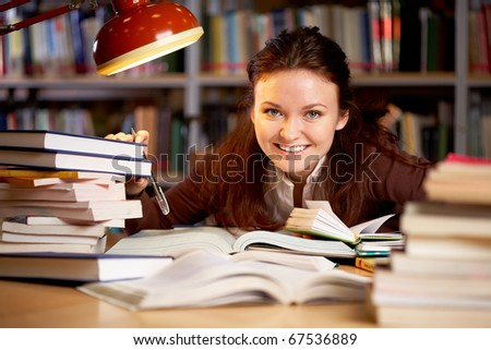 Portrait of young happy teacher sitting at the table and touching books - stock photo