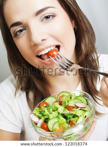 Portrait of young happy woman eating salad - stock photo