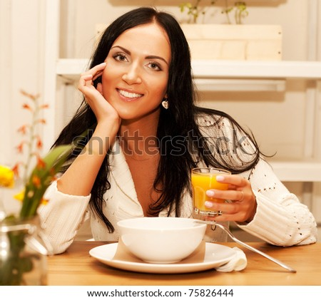 Portrait of young happy woman eating salad at home - stock photo
