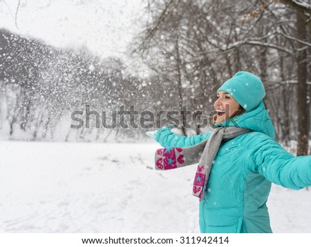 Portrait of young happy woman in blue jacket at the winter park. - stock photo