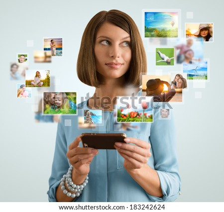 Portrait of young happy woman sharing her photo and video files in social media resources using her modern smartphone