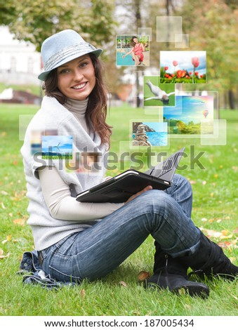 Portrait of young happy woman sharing her photo and video files in social media resources using her modern tablet computer - stock photo