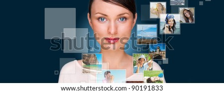 Portrait of young happy woman sharing his photo and video files in social media resources. Studio shot against blue background - stock photo