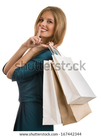 Portrait of young happy woman showing secret gesture with shopping bags, isolated over white background - stock photo