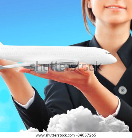 Portrait of young happy woman stewardess holding jet aircraft in her arms on foreground. Advertisement banner for transport companies - stock photo