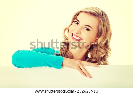 Portrait of young happy woman with blank board - stock photo