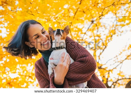Portrait of young happy woman with little cute dog in autumn park with yellow leaves