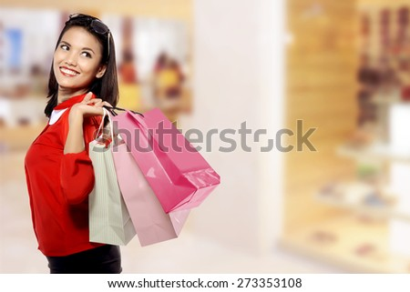 Portrait of young happy woman with shopping bags over blurred mall background - stock photo