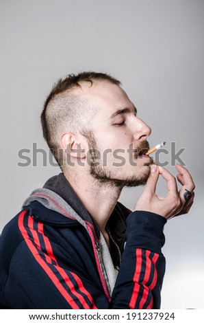 Portrait of young hipster man smoking cigarette