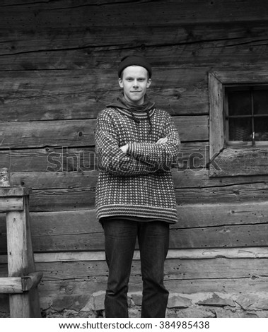 portrait of young hipster,  man with nose piercing  in front of old vintage wooden house