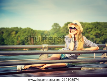 Portrait of Young Hipster Woman Relaxing in Park. Modern Youth Lifestyle Concept. Toned Photo. - stock photo