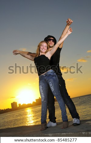 Portrait of young hispanic couple standing together against sunset background - stock photo