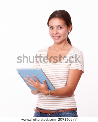 Portrait of young hispanic girl working on her tablet pc while standing and smiling at you on isolated white background