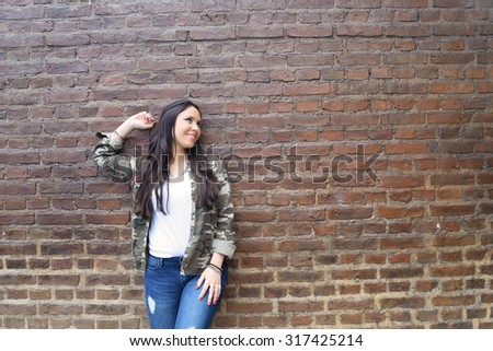 Portrait of young hispanic woman posing against a brick wall, looking up. Copyspace. - stock photo