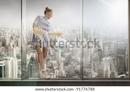 portrait of young hotel maid  washing glass on the big city background - stock photo