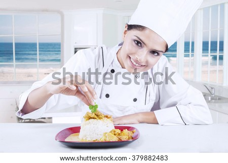 Portrait of young indian chef woman decorating delicious food in the kitchen
