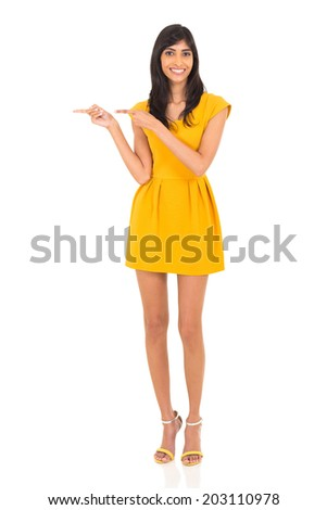 portrait of young indian woman pointing to the side on white background - stock photo