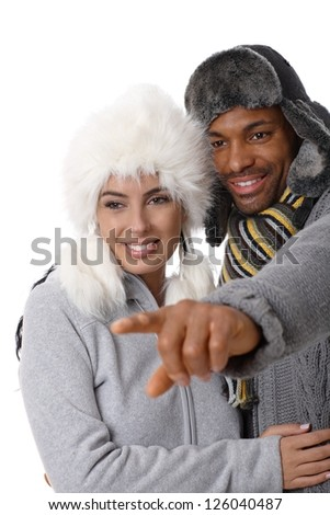 Portrait of young interracial loving couple at wintertime, man pointing to the distance, both smiling.