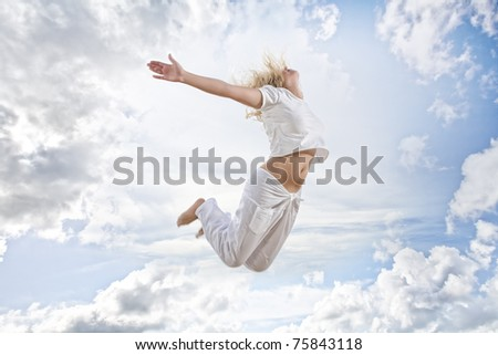 Portrait of young jumping woman on blue sky background - stock photo