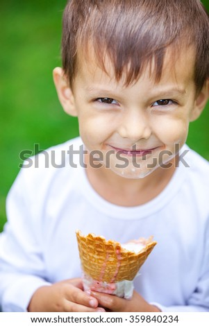 Portrait of young kid eating a tasty ice cream outdoor - stock photo