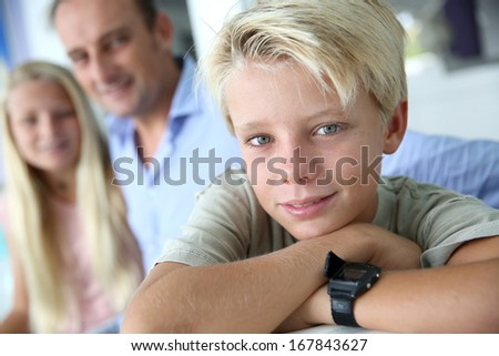 Portrait of young kid, family in background