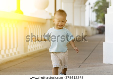 Portrait of young kid running and smiling outdoor in sunset. - stock photo