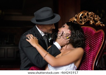 portrait of young kissing  happy couple of just married embracing and sitting on the red sofa in the luxury apartments