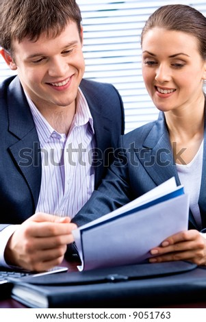 Portrait of young lady and business man looking at a document together