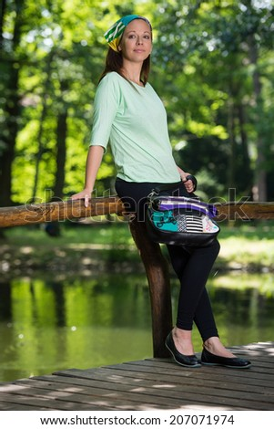 Portrait of young lady with handbag in the park - stock photo