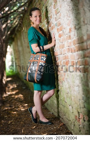 Portrait of young lady with handbag standing next to the wall - stock photo