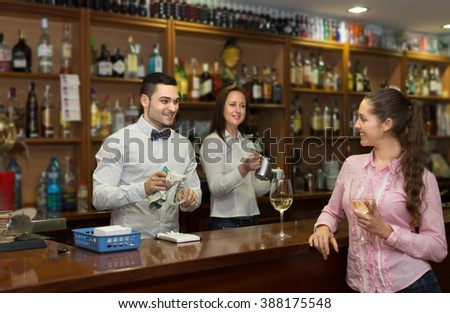 Portrait of young long-haired girl flirting with handsome barman at counter in bar. Selective focus