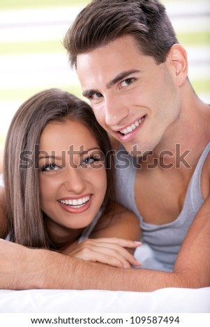 Portrait of young love couple embracing on bed and smiling - stock photo