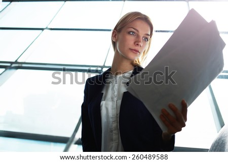 Portrait of young lovely business woman examining paperwork in light office interior sitting next to window, filtered image with flare sun light from the window - stock photo