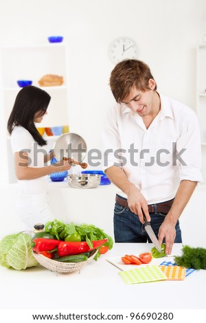 portrait of young lovely couple cooking in their kitchen, man slicing tomato happy smile - stock photo