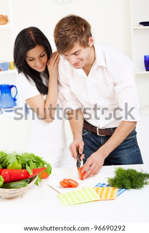 portrait of young lovely couple cooking slicing tomato in their kitchen, woman embrace, hug happy smile - stock photo