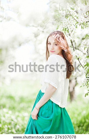 portrait of young lovely woman in spring flowers - stock photo