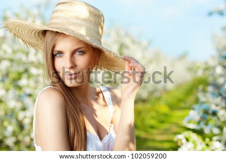 portrait of young lovely woman in spring flowers over amazing garden - stock photo