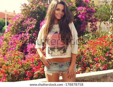 Portrait of young lovely woman wearing trendy t-shirt and shorts against pink spring flowers - stock photo