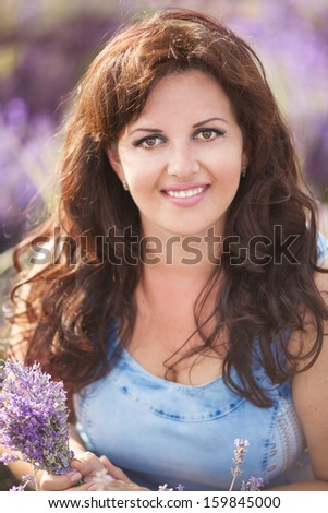 portrait of young lovely woman with lavender flowers, beautiful girl walking outdoors in lavender field, aromatherapy, France. Happy healthy woman smiling on nature and relaxing.