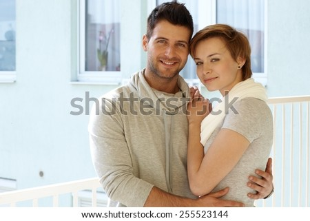 Portrait of young loving couple hugging in the terrace, smiling, looking at camera. - stock photo
