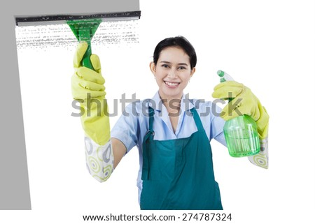 Portrait of young maid cleaning a mirror while wearing uniform, isolated on white background - stock photo
